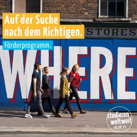 """Eine Gruppe junger Menschen läuft vor einer bunten Wand entlang, auf der """"WHERE"""" steht"""
