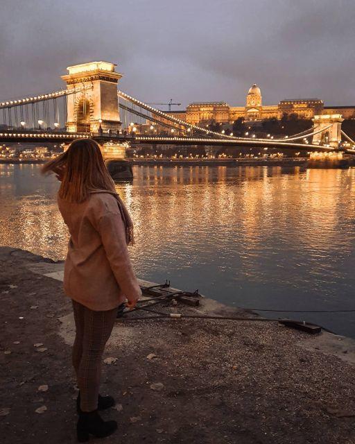 Ich stehe mit dem Rücken zur Kamera vor der beleuchtete Kettenbrücke bei Dunkelheit.