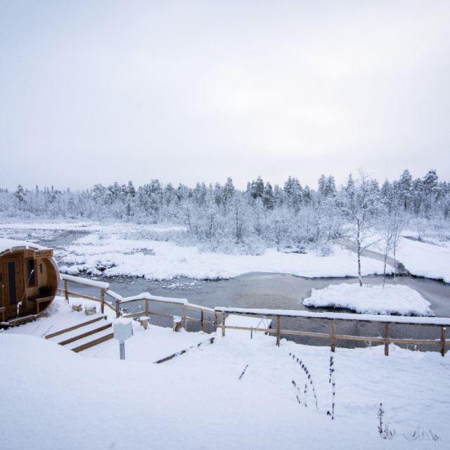 Ein Saunafass aus Holz vor der verschneiten Landschaft. Ein kleiner Steg mit Leiter am führt in den Fluss.