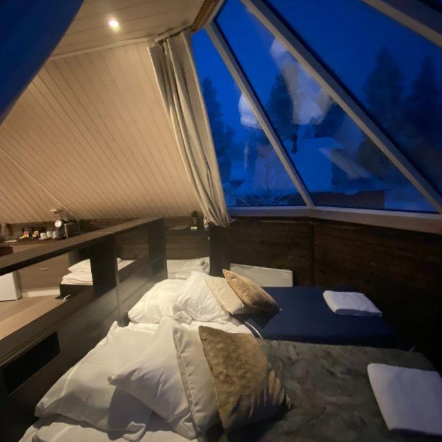 Eine gemütliche Hütte mit Panoramafenster über dem Doppelbett