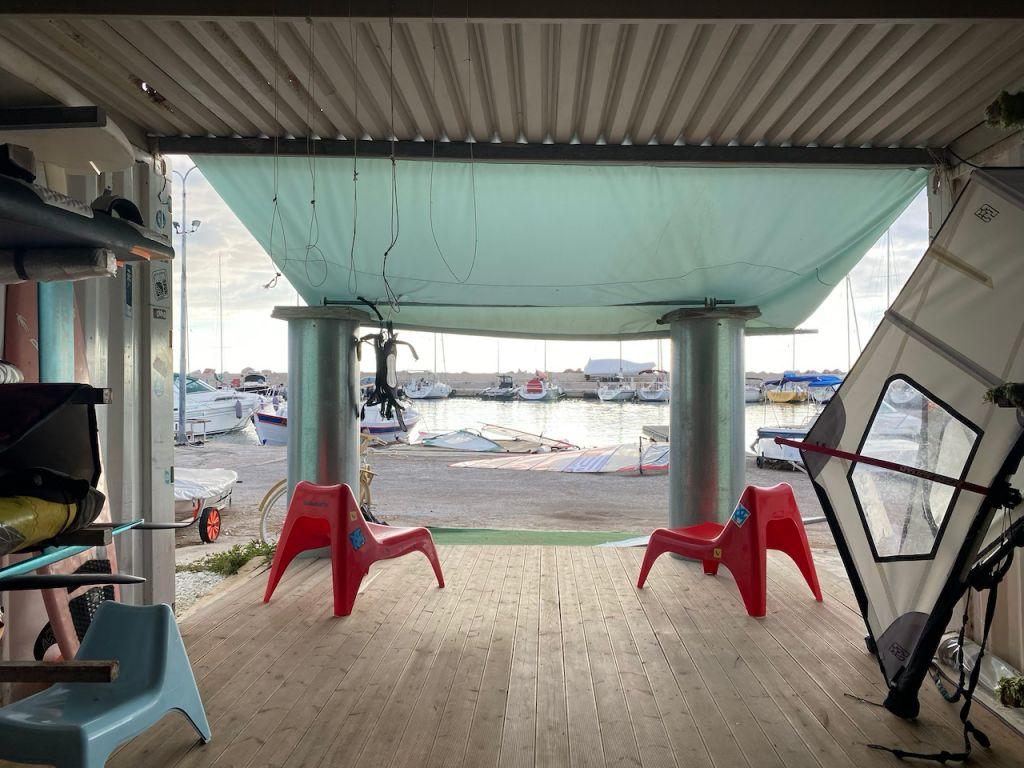 Das Foto wurde vom Inneren der Windsurfschule fotografiert. Zu sehen sind zwei rote Stühle, die in Richtung des Hafens im Hintergrund platziert sind.