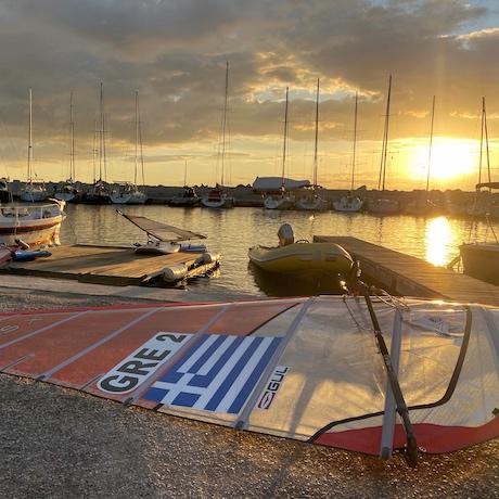 Im Vordergrund ist ein rotes Windsurfbrett mit einer Griechenland Flagge. Im Hintergrund ist der Hafen von Voula bei Sonnenuntergang zu sehen.