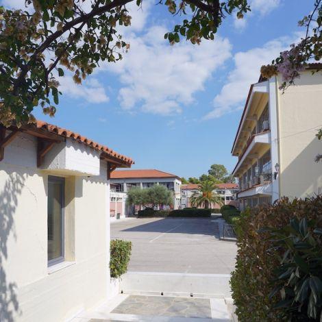 Blick auf die University of West Attica. Auf der linken Seite steht ein weißes Gebäude, auf der rechten Seite ist ein Bursch zu sehen. Im Hintergrund weitere Gebäude der Hochschule.