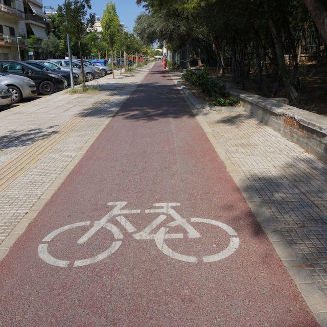 Zu sehen ist ein dunkelroter Fahrradwe, der in die Ferne führt. Im Vordergrund befindet sich ein großes weißes Fahrradsymbol.