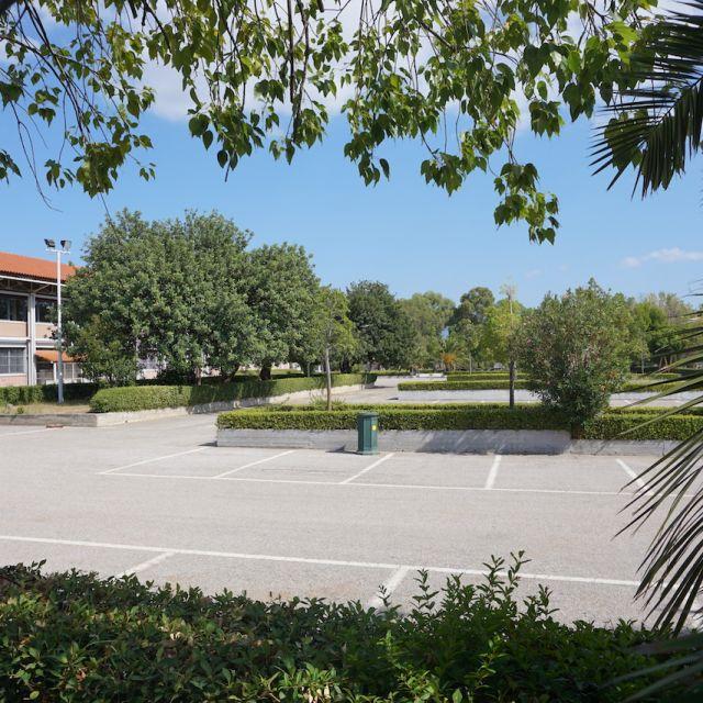 Ein Foto von dem Parkplatz der University of West Attica. Der Parkplatz ist leer, nur Bäume und ein Gebäude auf der linken Seite ist zu sehen.