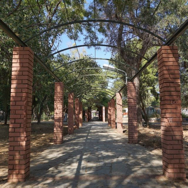 Durch die Mitte führt ein betonierter Weg, der rechts und links von braunen Säulen umrandet ist.