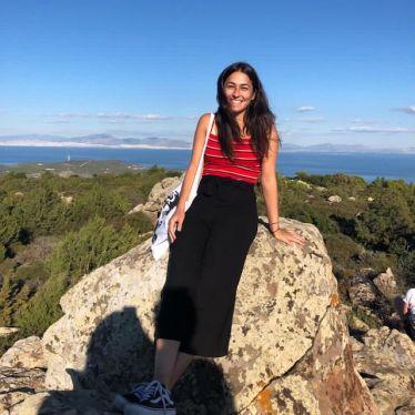 Ein Bild von mir Sitzens auf einem Felsen. Im Hintergrund ist die Landschaft der Insel Ägina und das Meer zu sehen.