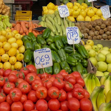 Verschiedenes Obst und Gemüse wie Tomaten, Paprika, Kartoffeln und Zitronen. Zwischen dem Obst und Gemüse befinden sich Preisschilder.
