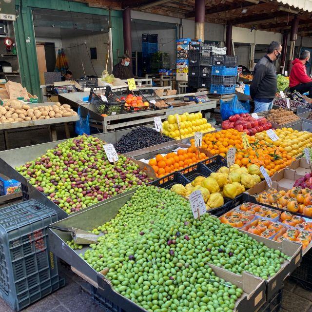 Kästen gefüllt mit Obst und Gemüse wie Zitronen, Tomaten und Orangen. Im Vordergrund ist ein Haufen grüner Oliven zu sehen.
