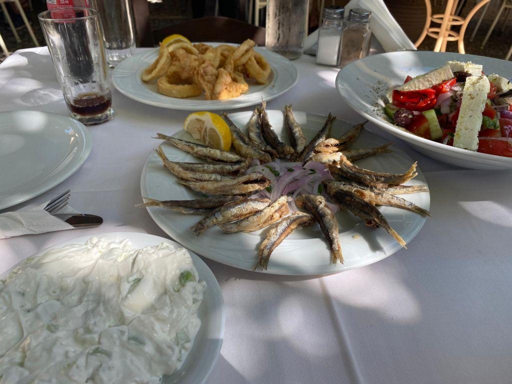 Ein Tisch mit mehreren Tellern gefüllt mit kleinen Fischen, Salat und Tsatsiki.