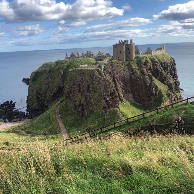 Burgruine auf felsiger Landzunge, vorne grüne Gräser, im Hintergrund das Meer