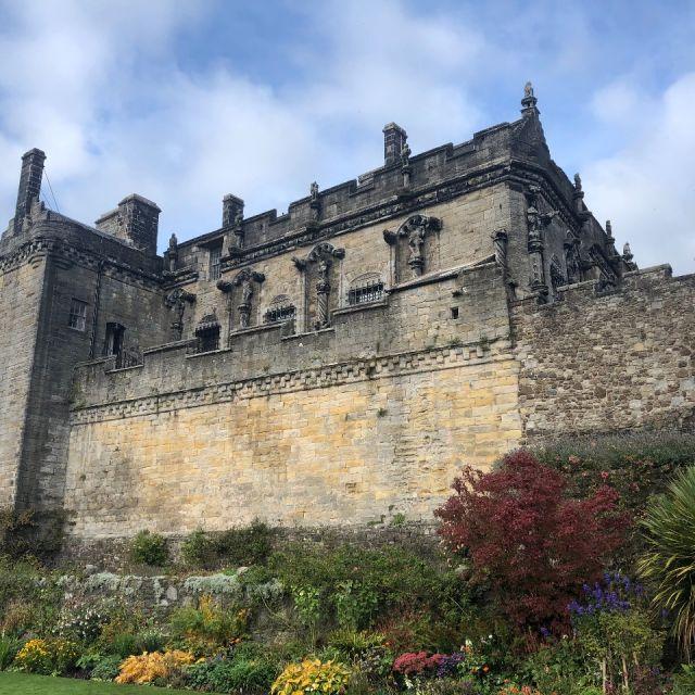 Bepflanzter Garten, in dem eine steinerne hohe Burg liegt, blauer Himmel