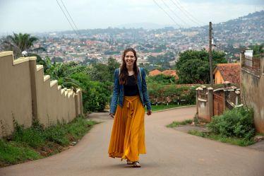 Lara läuft eine Straße in Uganda hinauf.