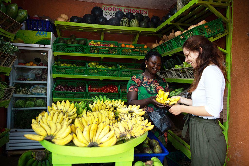 Lara kauft Obst an einem Stand in Kampala.