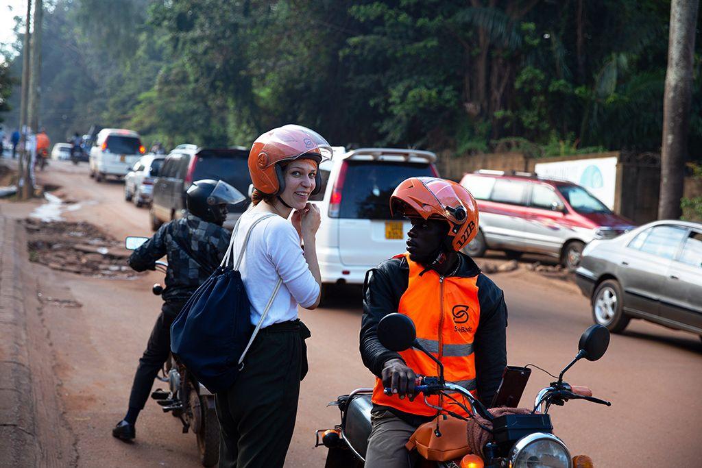 Lara steht neben einem Motorradtaxi auf einer Straße in Kampala.
