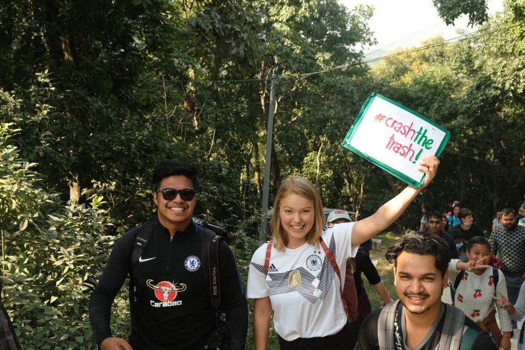 Lara und Freunde beim Müllsammeln auf einem Wanderweg. Lara trägt ein Schild mit der Aufsschrift #CrashTheTrash