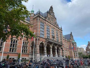Auf diesem Bild sieht man das Gebäude der Rijksuniversiteit Groningen. Es ist ein altes, hohes Gebäude, das rot gepflastert ist. Vor der Uni stehen Fahrräder.