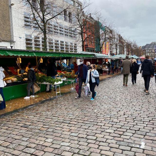 Man sieht einen Stand auf dem Markt auf dem frisches Obst und Gemüse verkauft wird.