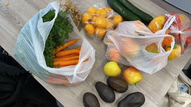 Man erkennt Einkäufe - hauptsächlich Obst und Gemüse - die auf dem Tisch liegen.