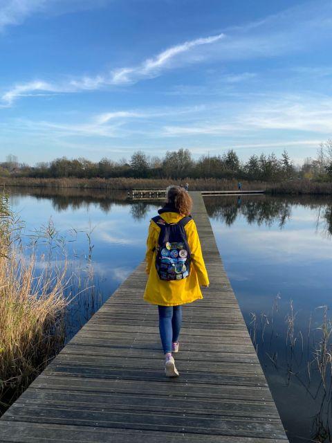 Man sieht einen Steg, der über einen See verläuft.Man sieht eine Frau mit gelber Regenjacke mit dem Rücken zur Kamera.