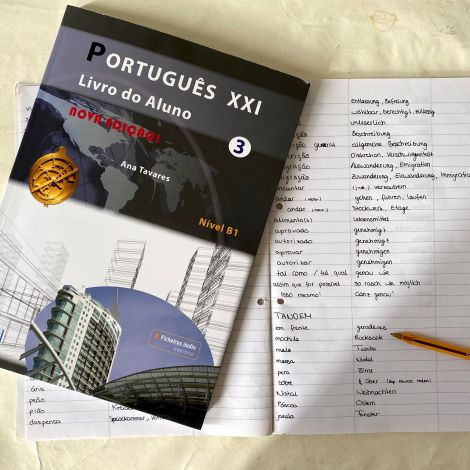 Mein portugiesisch Buch liegt auf dem Schreibtisch, sowie mein aufgeschlagenes Vokabelheft.