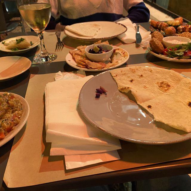 Auf dem gedeckten Tisch befinden sich unterschiedliche orientalische Gerichte in kleinen Portionen angerichtet.