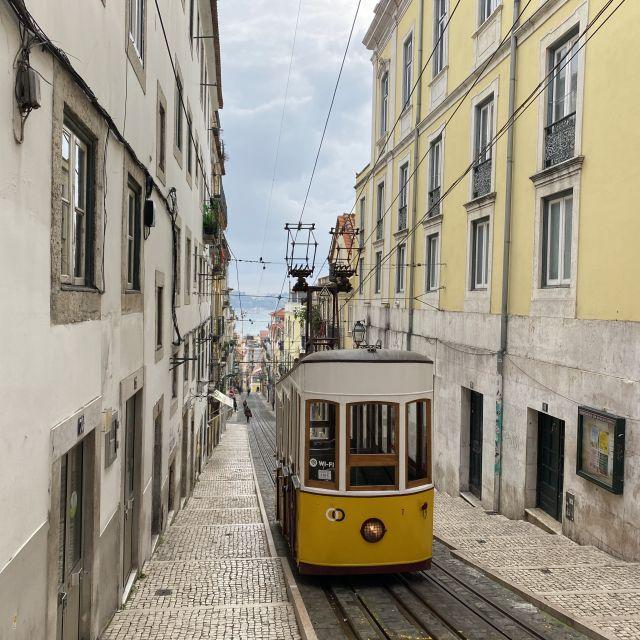 Eine gelbe Straßenbahn fährt durch eine schmale Gasse in Lissabon.