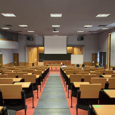 Ein Hörsaal der Uni in Lissabon. Vorne steht das Rednerpult mit Leinwand, davor sind eine Reihe von (noch) leeren Sitzen