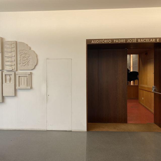 Eine große Holztür, dahinter der Hörsaal. An der Wand hängt eine künstlerische Collage aus Stein.