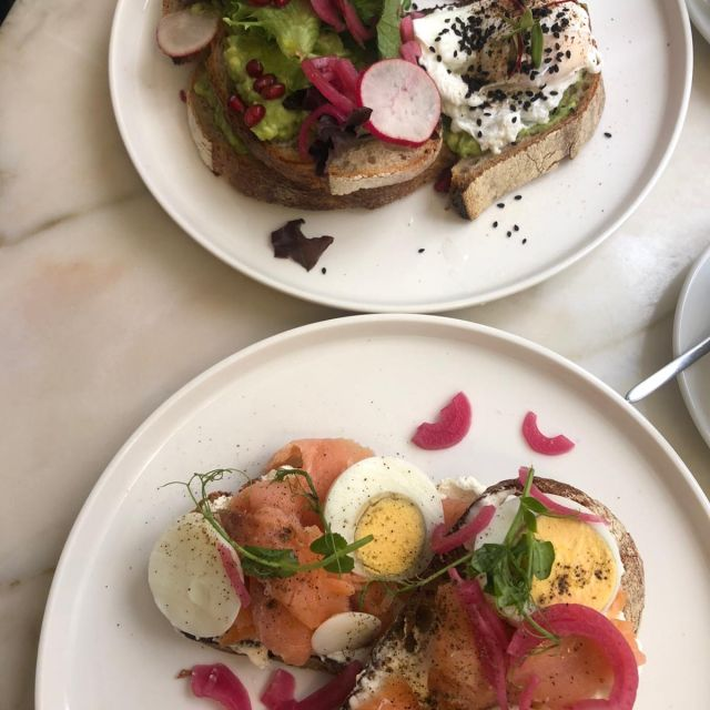 Zwei schön angerichtete Teller, einmal mit einem Avocadotoast und einmal Lachsbrot mit Ei