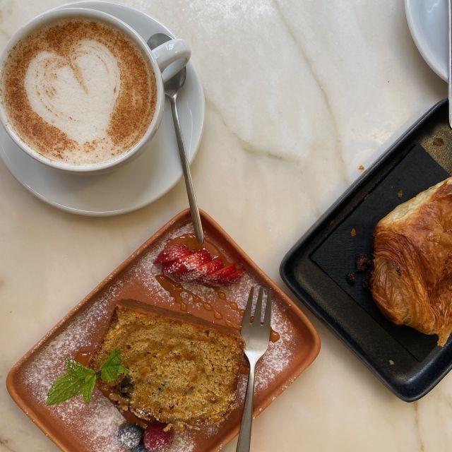 veganer Karottenkuchen mit Beeren angerichtet, dazu eine Tasse CHai-Latte, verziert mit einem Schaumherz.