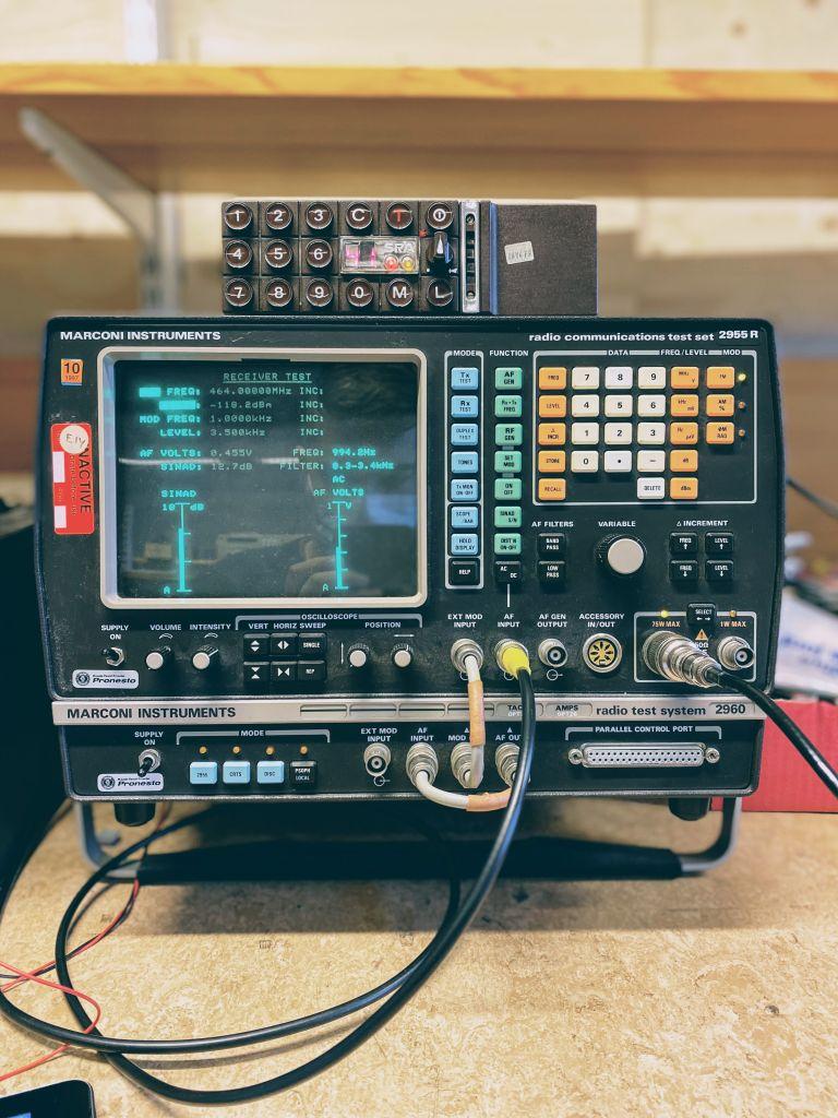 Messinstrument aus der Drahtloskommunikationstechnik mit einem Display, vielen Tasten und angeschlossenen Kabeln.