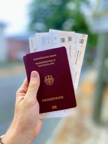 Hand hält Reisepass mit Bahnfahrkarten in die Luft