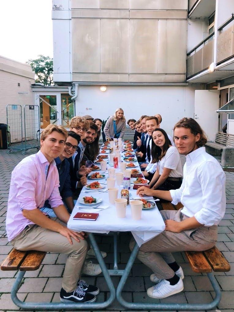 Einführungssittning mit unseren Mentoren aus. Dabei wurden wir in die verschiedenen Traditionen bei einem Sittning eingeweiht. Die Studierenden sitzen zusammen in Rahmen eines Sittnings an einer festlich gedeckten Tafel im Freien.