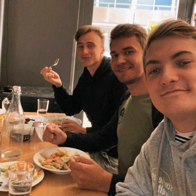 Drei Studenten sitzen an einer langen Tafel beim Mittagessen. Auf den Tellern sieht man Nudeln , Salat und Brot.