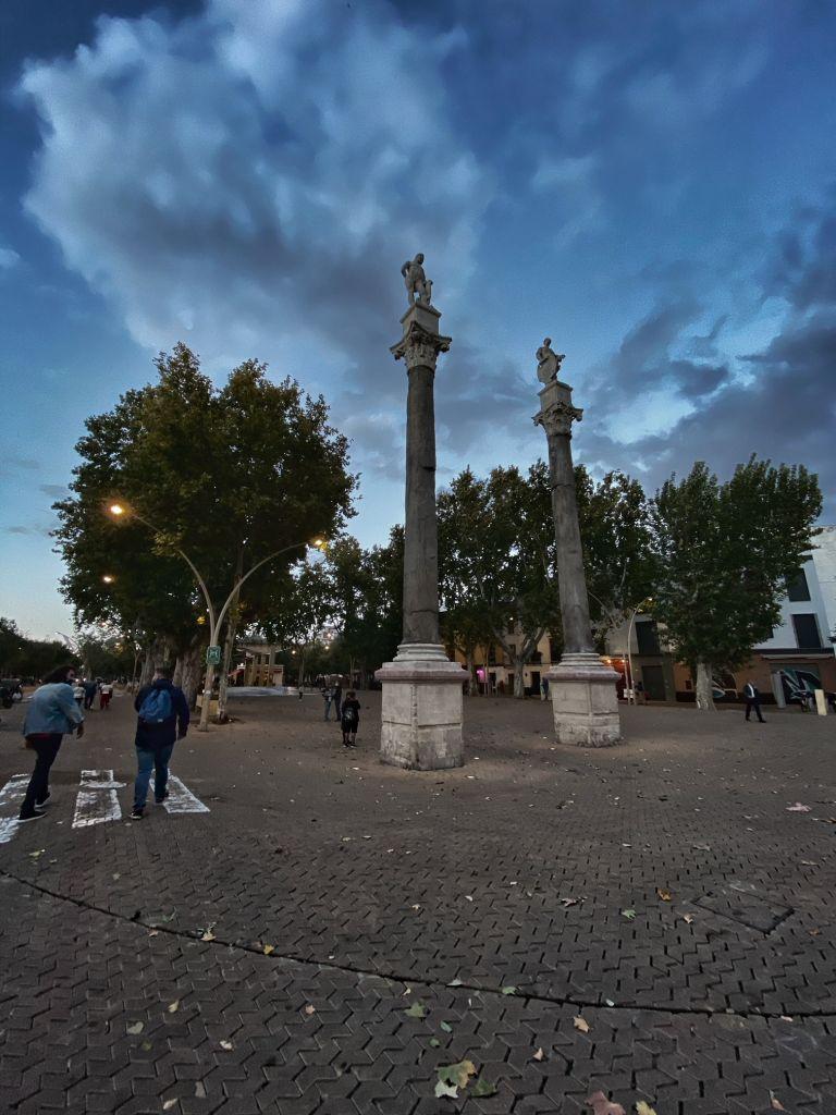 Zwei römische Säulen am Anfang der Allee mit Bäumen rechts und links.