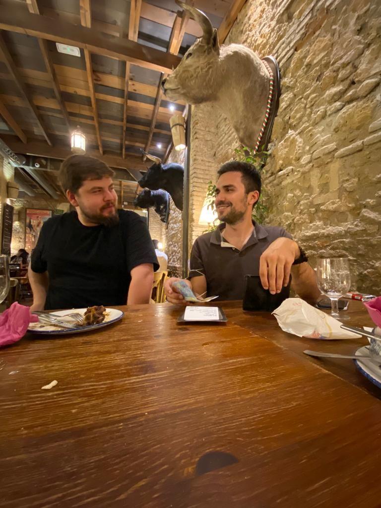 Zwei Jungs am Kneipentisch vor der Rechnung. Einer mit Geldscheinen in der Hand. Ein Stierkopf an der Wand.