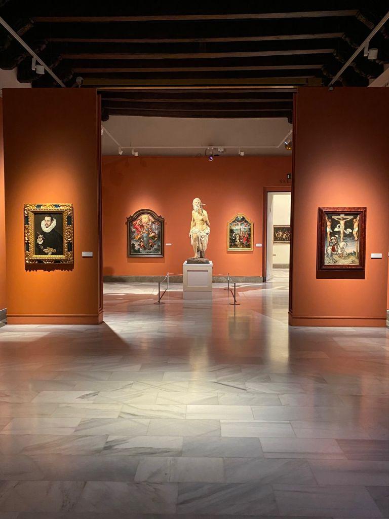 Rote Wände mit vier Gemälden und einer Figur eines Mannes.