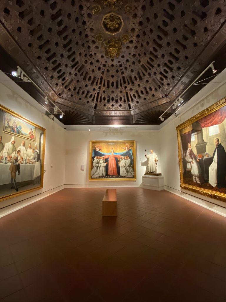 Weiße Wände, drei große Gemälde, Sitzbank in der Mitte, verzierte Decke.