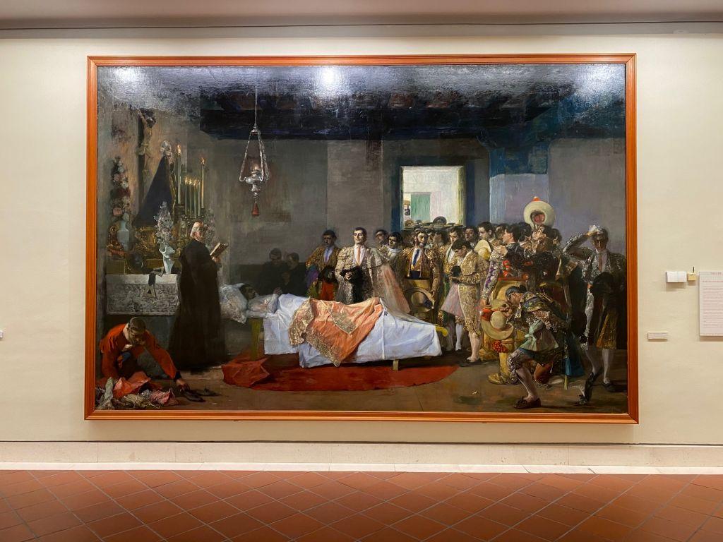 Gemälde. Ein Mann liegt im Bett, ein Geistlicher steht daneben. Ihm gegenüber tummeln sich viele Männer in goldenen Torrerouniformen.