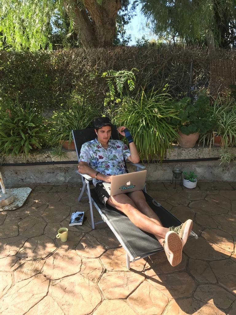 Junger Mann sitzt mit kurzer Hose und blauem Hemd sitzt auf einer Liege im Garten mit Laptop auf dem Schoß.