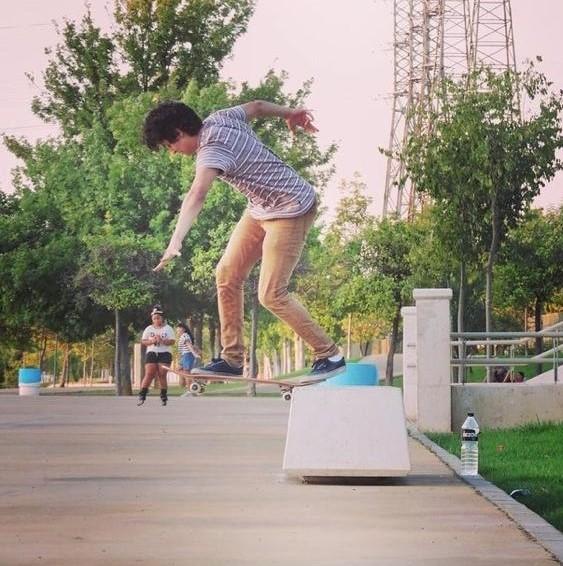 Junger Mann mit beiger Hose springt gerade auf dem Skateboard von einem weißen Betonklotz.