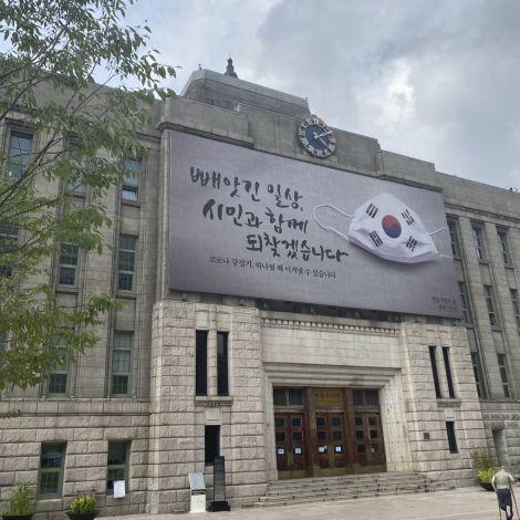"""Ein großes Schild zeigt eine Maske mit Koreaflagge und die Aufschrift: """"Weggenommener Alltag - werden wir gemeinsam mit den Bürgern wiederfinden"""""""