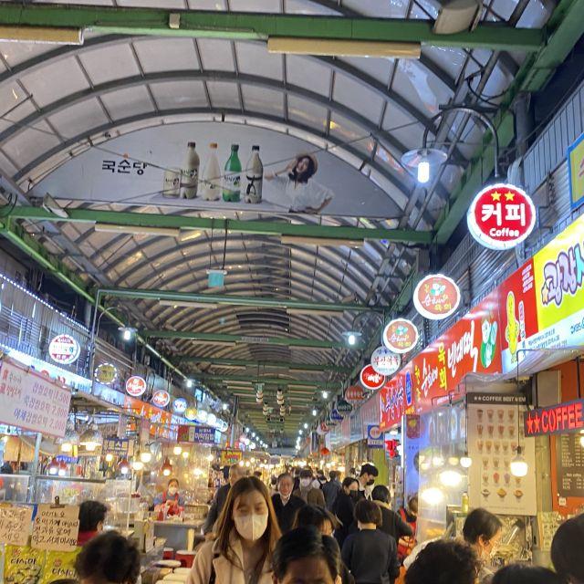 Eine Markthalle mit vielen Essensständen und vielen Menschen