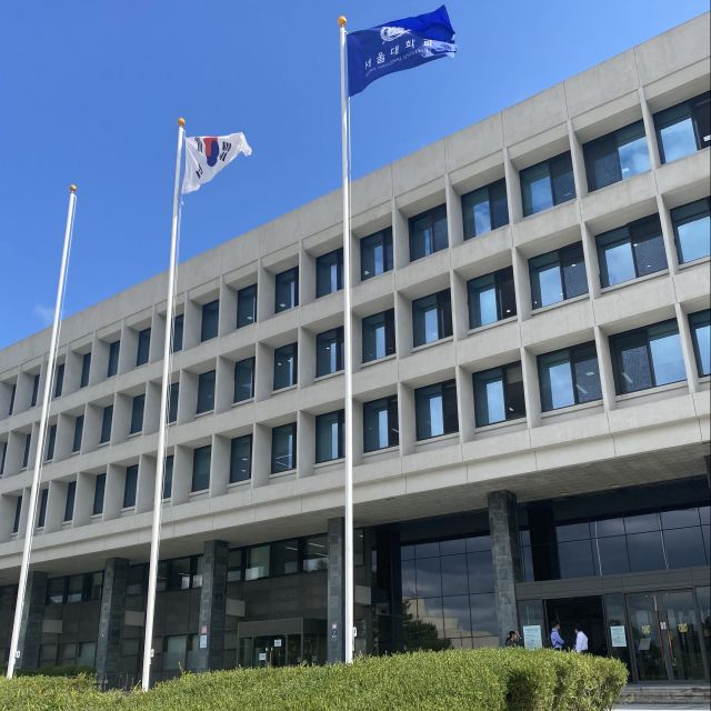 Vor einem großen Verwaltungsgebäude sieht man die südkoreanische Flagge sowie eine mit SNU Logo