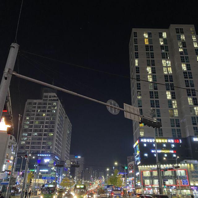 Eine hell beleuchtete Verkehrskreuzung zwischen hohen Gebäuden nachts.