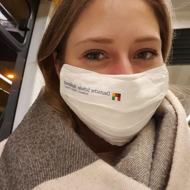 In der Bahn mit einer Mund und Nasenmaske von der Deutschen Schule Budapest.