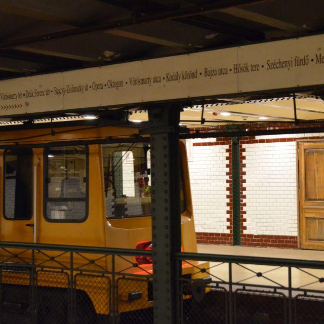 Auf einer länglichen Tafel sind die Stationen der M1 aufgeschrieben und eine gelbe Bahn fährt am gegenüberliegenden Gleis ab.