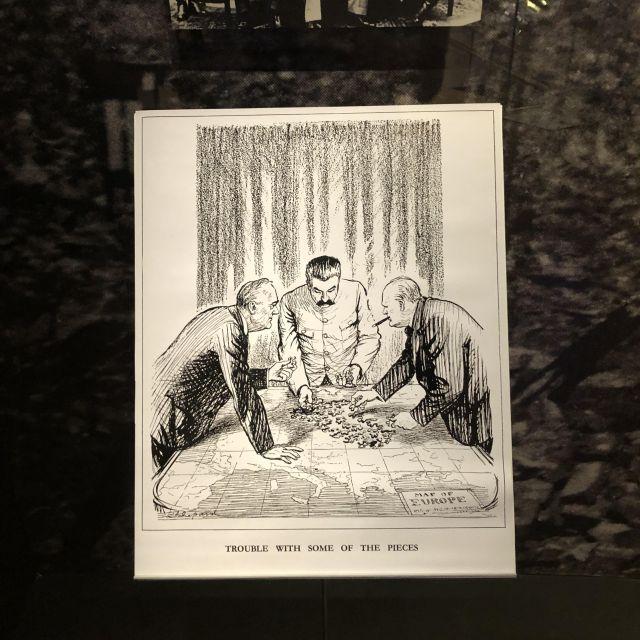 In einer Karikatur beugen sich Stalin, Churchill und Roosevelt über eine Landkarte mit Puzzleteilen