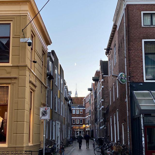 Hier sieht man eien Straße gesäumt von niederlänischen Häusern. Am Himmel steht der Mond.
